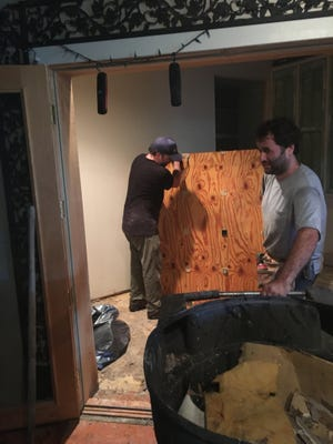 Musicians work to remove wet material from Dockside Studio in Maurice, which sustained two feet of water in the recent flood.