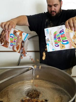 Kaweah Brewing co. head brewer, Julian Sprague pours flavored cereal in his brew mixture.
