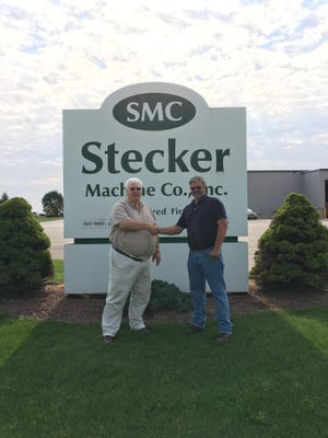 File - Employees stand in front of a sign for Stecker Machine Company.