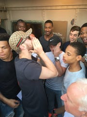 Western Michigan guard and Laingsburg grad Ryan Wade, center, is overcome by emotion after learning he received a full ride scholarship for the season on top of the Eiffel Tower earlier this week.