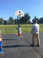 Mentors and students playing basketball at opening day.