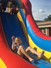 Mentor Katie Cates makes her way down the bounce house slide.