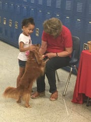 Kihanna Singleton, age 4, and Joanne Minnich pet Copper, on Saturday at the Autism Awareness Fair at Chambersburg Area Middle School South