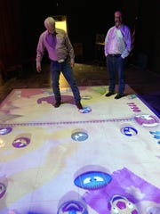 Jim McPherson, left, owner of Kids Fit and Fun, demonstrates his hockey skills in a video game projected on the floor from an overhead projector.