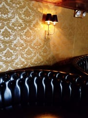 The Womack features gold flocked wallpaper and black