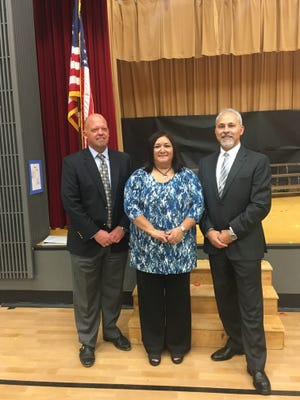 Gloria Pereyra-Robertson, center, of Howard Elementary School in Medford, Oregon, won the 2017 Teacher of the Year award on Wednesday, September 28, 2016. Medford School District Superintendent Brian Shumate, left, and Deputy State Superintendent Salam Noor, right, surprised her with the award.