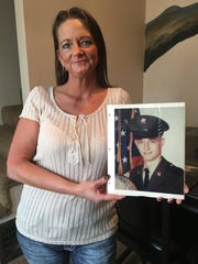 Dena Heavrin holds a picture of her father, Mark Heavrin, who died in Vietnam.
