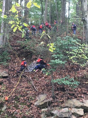 Emergency responders in Boonton lift a teen boy to safety near Grace Lord Parkafter the boy slipped halfway down the 60-foot drop and was stuck on a rocky ledge. Oct. 2, 2016