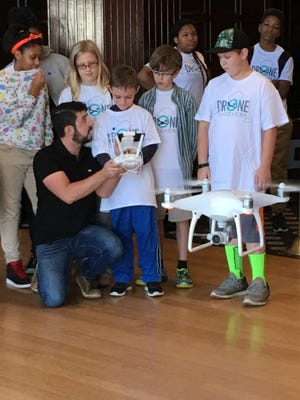 Edward Kostakis, a senior pilot at DJI, hands the controls to a Phantom 4 drone to Duncan Beall, 9, of West Friendship, Md., during the 4-H National Youth Science Day on Oct. 5, 2016, at the National Press Club in Washington, D.C.