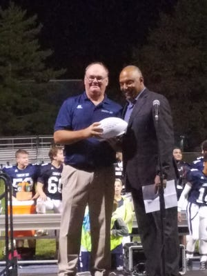 Former Cincinnati Country Day head coach Tim Dunn is honored during halftime of CCD's win vs. Clark on Friday, Oct. 7. At right is Cincinnati Bengals head coach Marvin Lewis.