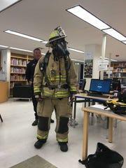 Senior Dominic Rodriquez tries on a firefighter suit
