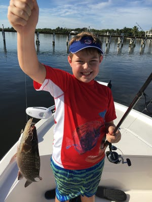 Cameron with one of many snapper he caught while fishing docks and mangroves in Fort Pierce!