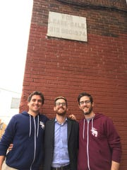 Eastern Market Brewing Co. co-founders Paul Hoskin, Dayne Bartscht and Devin Drowley stand Oct. 12, 2016 under the faded sign they called to inquire about the building that would become their brewery's home on Riopelle in Eastern Market.