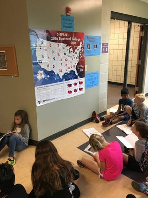 In this photo provided by Halie Miller, taken Sept. 26, 2016, students in Halie Miller's fourth grade class at Glacier Ridge Elementary School in Dublin, Ohio, use an Electoral College map to create different combinations of numbers to get to the magic number of 270 electoral votes needed for victory as part of a math assignment.