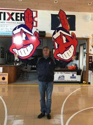 Lifelong Indians fan Jeff Burkhart of Lexington poses with two Chief Wahoo decorations.