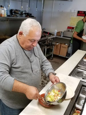 Raffi Manna, chef and owner of Raffi's Oasis Cafe, prepares a Mediterranean salad to serve alongside a shawarma sandwich. This week, Manna will begin offering special dishes from his former Italian restaurant, Raffi's.