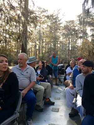 Shane Eddy (standing in back) with Champagne's Cajun Swamp Tours leads a group through the swamps and bayous of Lake Martin on Saturday.