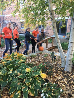 Kaitlyn Hodkiewicz points out her brother's flower at the Ronald McDonald House's Secret Garden, while her classmates look on. From the left, they are, Kaylee Huberty, Meckenna Portier, Hodkiewicz, Brianna Sylvester and Michele Bushmaker.