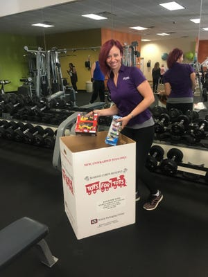 Rececca Kolva, a trainer from Anytime Fitness, accepts a donation for Toys for Tots at the Hopewell location. Toys will be collected through Dec. 7 at area Anytime Fitness locations including: 301 S. Main Road, Vineland; 1601 N. High St., Millville; and 597 Shiloh Pike, Hopewell.