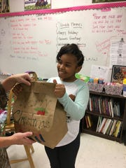 Kennedy Woods presents the gift bag she made as NEHS sponsor Michelle Kinggard's reaches in to help her fold it tightly before the next step of punching holes and running a ribbon through the top.