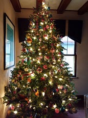 Michael McKinley decorates his Christmas tree with a collection of vintage ornaments from the 1950s and '60s.