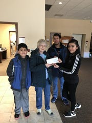 Students in each grade level at Sheboygan's Farnsworth Middle School raised nearly $458 for a local food pantry in a recent Penny War. Pictured with the food pantry director are students Jose Gutierrez, Brandon Alvarez and Daniella Cortes.