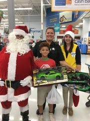 Garden Terrace Boys & Girls Club member poses with St. Lucie County Sheriff's deputy, Santa and a Wal-Mart associate during Shop with a Cop.