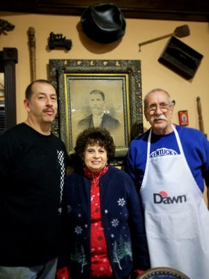 """Sean, Cathy and Don Powers stand in front of an old photograph of many """"great"""" grandfather Berry. Almost all the items on the walls have a family history."""