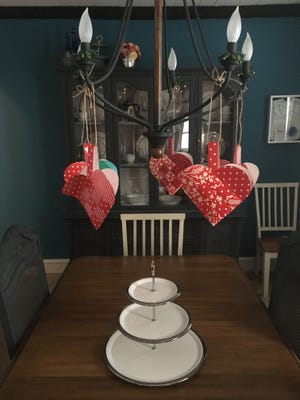 Nordic paper hearts hang from a chandelier. The hearts are both an example of hygge decor and a great craft to learn prior to Valentine's Day. You can learn to make them at the Philadelphia Home Show.