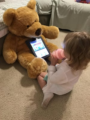 Isabella watches a YouTube video with Mr. Big Bear while enjoying a bottle before bed recently.