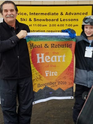 "Peter Jucker, left, owner of Ober Gatlinburg, stands with a student from Jefferson Middle School and the ""Heal and Rebuild"" flag students signed in support of the ski mountain and those affected by the Gatlinburg fires."