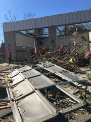 Hattiesburg firefighters sift through what is left of Fire Station 2 after the building was destroyed by an EF3 tornado early Saturday morning. Three firefighters were inside during the storm, but none were harmed.