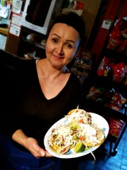 Angelica Medina holds a plate of sopes -- crunchy corn boats filled with meat, cheese, lettuce, tomato and crema.