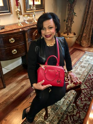 GO RED Dr. Mureena Turnquest-Wells is shown with a Michael Kors bag filled with jewelry, a scarf, hat and most importantly, Godiva chocolate. This beautiful ensemble can be yours at the Feb. 17 Go Red luncheon, sponsored by Deaconess Heart Hospital and benefiting the American Heart Association. For more information, call Malissa at 270-929-9585.