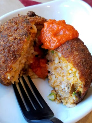 Arancini are dense orange-sized balls of risotto flavored with meat and peas, coated with crumbs and fried until crisp. Served with tomato sauce, they can be an appetizer or main course.