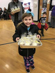Julianna Uccello arrives with baked goods at the Kennedy Elementary School's Pajama Dance-a-Thon .
