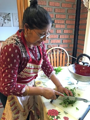 League of Kitchens instructor Afsari Jahan chops parsley for a recipe.