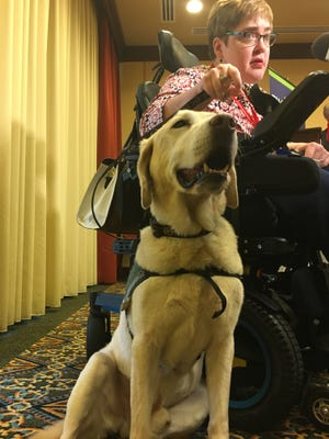 Stephanie Miner sits with her dog, Astro,  just minutes after becoming the first Enable Alabama account owner during the Alabama disABILITY Conference at the Renaissance Montgomery Hotel and Spa at the Conference Center on Monday, Feb. 27, 2017.