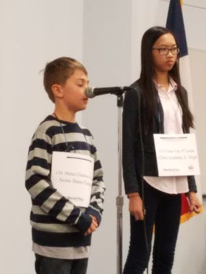 Malec Chambers of Notre Dame Elementary School prepares to spell a word in a final round of the 33rd Annual Regional Spelling Bee. Celine Yap, right, of Christ Academy, won the bee in the 25th round.