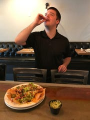 Shift supervisor and bartender Julien Scott samples some of the restaurant's smokin' nachos. Owner Mitch Fletcher said he wants his menu to reflect the kinds of dishes he and his staff like to eat themselves.