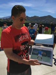 Dan Mihailesco from Toronto shows off his binder full of autographed tennis pro pictures at the BNP Paribas Open. (March 9, 2017)