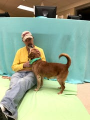 Pablo, one of the animals rescued from a hoarding situation, hangs out with Vanderburgh Humane Society volunteer Mark Williams on Thursday.
