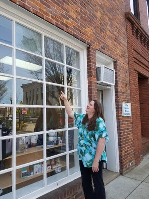 The Water Store owner Janelle Sterrett points at a hole in her window where a hawk flew through.