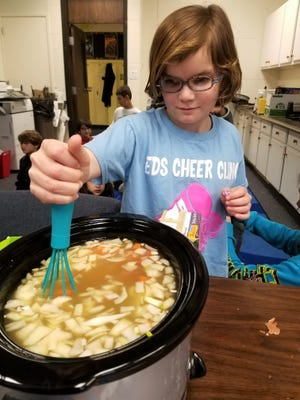 Greta Griffin, a fourth grader at Evansville Day School, stirs a pot of pea soup to make sure the peas are not stuck together before the lid goes on.