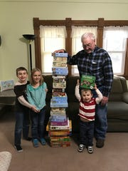 A stack of puzzles at columnist Susan Manzke's home tower over her grandchildren Eli, Arianna and Wyatt.