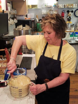 Becky Reynolds stirs up a batch of butter pecan fudge at her Grand Rivers Fudge Factory.