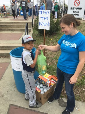 Amy Williams and her son Dri worked to collect food for Pack the Pounds at White House City Park on Saturday, April 1, 2017