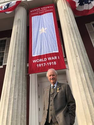 Ocean County Freeholder John C. Bartlett Jr. in front of a banner with a star for every resident who served in World War I and a gold star for every resident who did not come home.