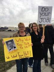 Robin Stone, left, and Sharie Kernan, of Manchester, protest outside a closed event with U.S. Rep. Rod Blum in Cedar Rapids.