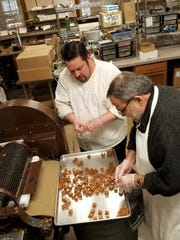 Joest squares up pieces of the cut caramel with help from Stephen Libs.